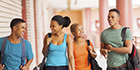 group of cheerful african college students walking in building corridor
